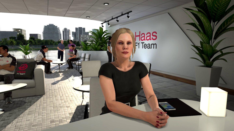 Screenshot: Eine blonde Formel 1 Managerin sitzt in einer Lobby an einem Tisch