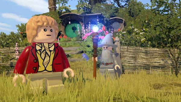 Bilbo und Gandalf stehen auf einer Wiese.