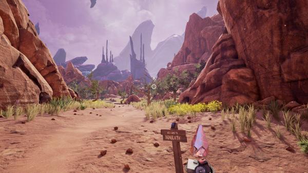 """Screenshot: Canyonlandschaft mit vereinzelten Stauden und Bäumen. Im Hintergrund sind außerirdische Gesteinsformationen. Im Vordergrund steht eine Holztafel auf der """"Welcome to Hunrath"""" steht."""