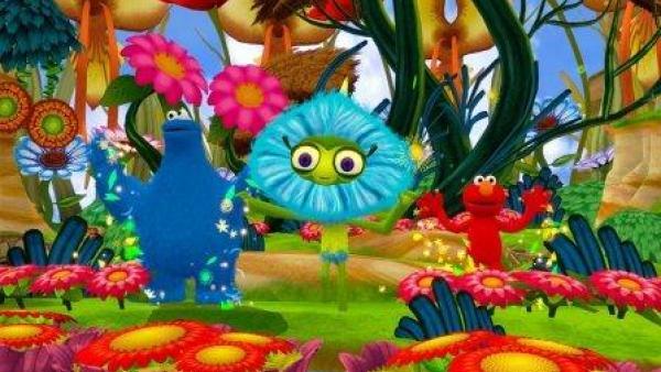 Drei Figuren der Sesamstraße in bunter, fröhlicher Umgebung.