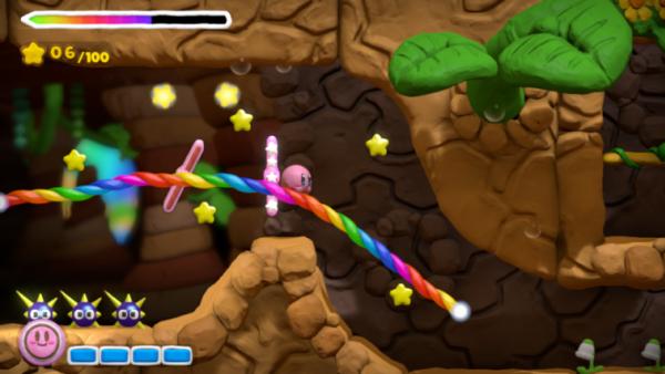 Screenshot: Kirby gleitet an der Regenbogenschnur (buntes Seil) entlang