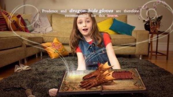 Ein Mädchen sitzt vor dem Zauberbuch und staunt über die Zaubereien.