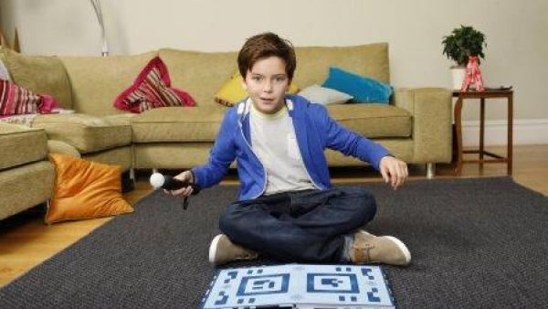 Ein Junge sitzt mit dem Move-Controller vor dem Buch.