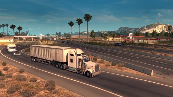 Screenshot: Ein Truck fährt in einer karg bewachsenen Landschaft auf eine Autobahn auf.