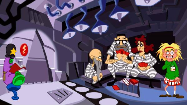 Screenshot: Drei Gefängnisinsassen sitzen beim Kartenspielen. Rechts neben ihnen steht die Hauptfigur Laverne während im linken Eck ein purpurfarbenes Tentakel als Aufpasser gekleidet in einem Buch liest.