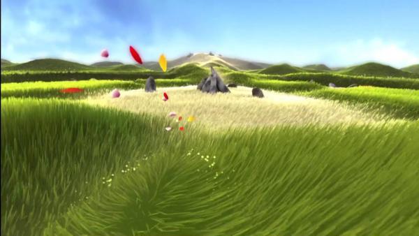 Gras wird zur Seite geweht, im Hintergrund ein dürres Areal