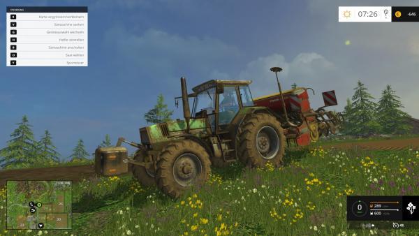 ein verschmutzter grüner Traktor fährt mit einem Anhänger zum Säen über ein Feld