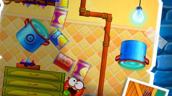 Screenshot: In einem Level in einer Küche schneiden die zwei kugelrunden Spielfiguren Grimassen.
