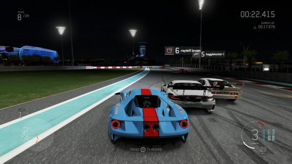 Screenshot: Ein gestreifter Sportwagen fährt bei Nacht beinahe auf gleicher Höhe mit zwei Gegnern auf eine Kurve zu