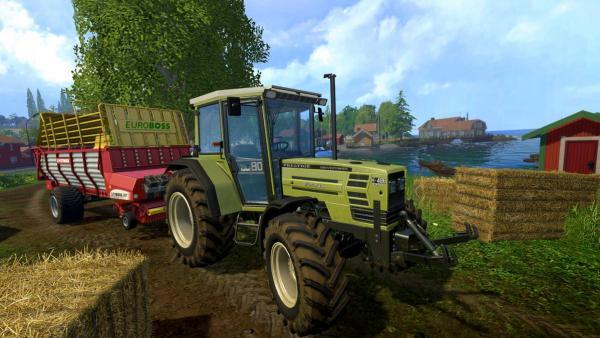 ein grüner Traktor steht mit rot/gelbem Anhänger zwischen Heuballen