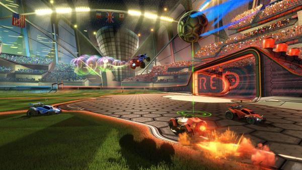 Screenshot: Der Ball wirbeld durch die Luft, während vier Autos vor vollbesetzten Tribünen um seine Aufnahme fahren