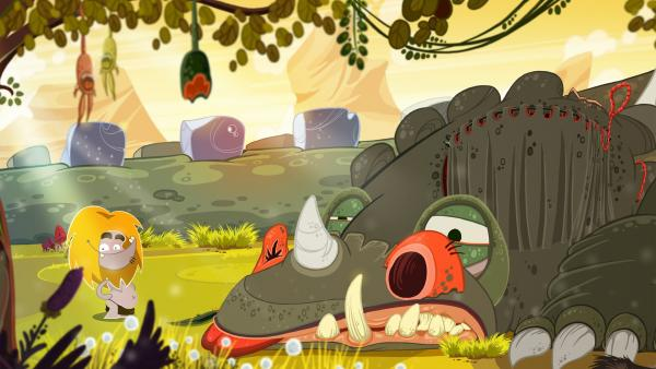 Screenshot: Ungh vor einem riesigen steinzeitlichen Tier auf einer grünen Wiese