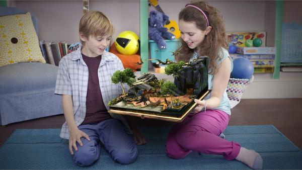 Zwei Spielende mit Wonderbook und Darstellung eines Waldes mit Dinosauriern als erweitere Realität