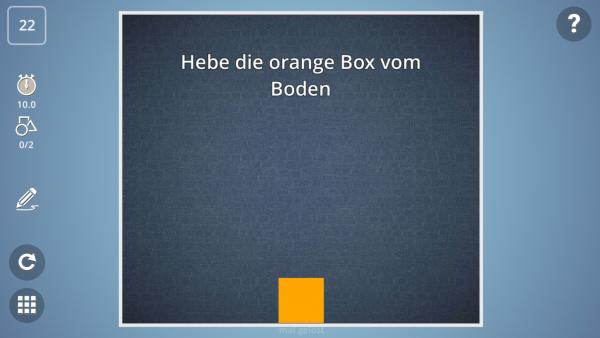 """Screenshot: Eine orangerne Box in einem Raum mit der Spielanweisung """"Heb die orangene Box vom Boden""""."""