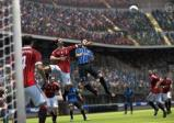 Fußballspieler springen dem Ball entgegen.