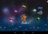 Screenshot: Die Maus steht auf einer Rakete und schwebt im Weltall. Um sie herum fliegen Asteroiden und ein kleiner Satellit.