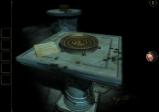 """Screenshot von """"The Room Two"""" mit einem Steintisch und einer goldenen Platte"""