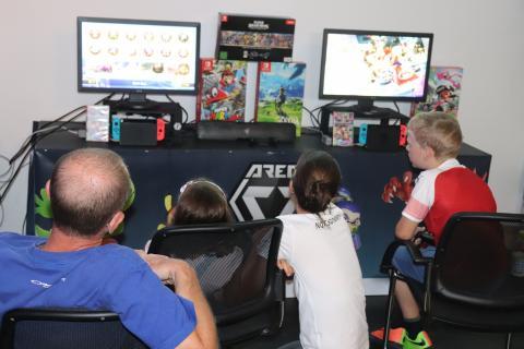 2 Kinder spielen an einer Konsole, 2 Erwachsene sehen zu