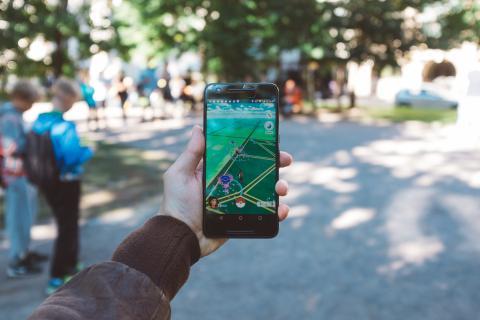 Junge Hält ein Smartphone, man sieht nur seine Hand und den Bildschirm.