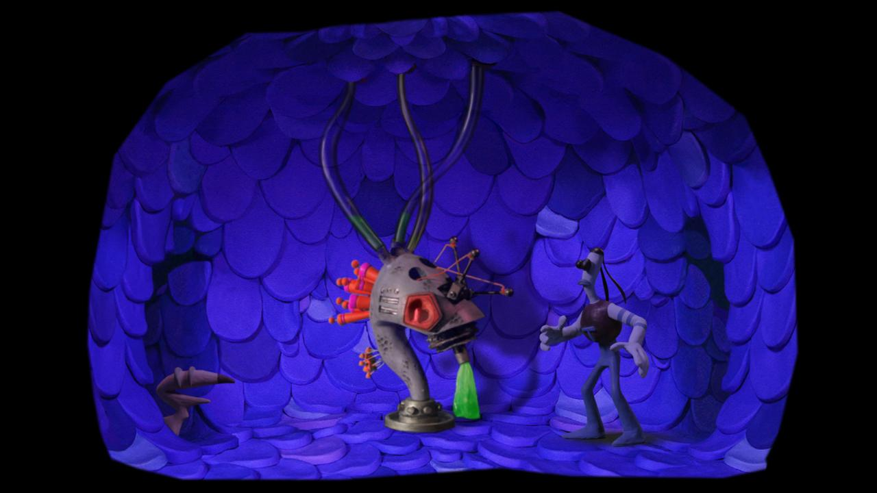 Screenshot: In einem runden Raum stehen die beiden Figuren vor einer nicht identifizierbaren Maschine